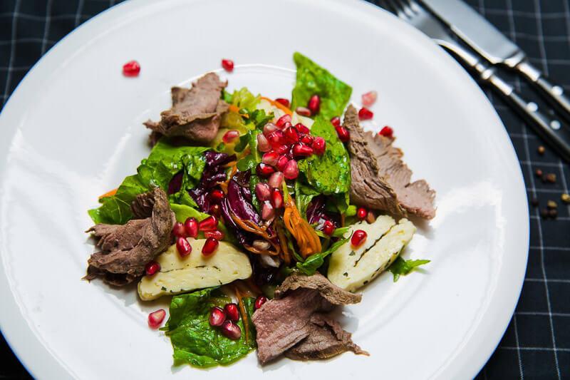 Теплый салат с ростбифом, копченым халуми и гранатовым соусом