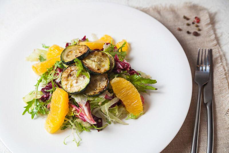 Итальянский салат Milano с фенхелем, апельсином, жаренными цуккини, грецкими орехами и цветами фиалки под соусом «Винегрет»