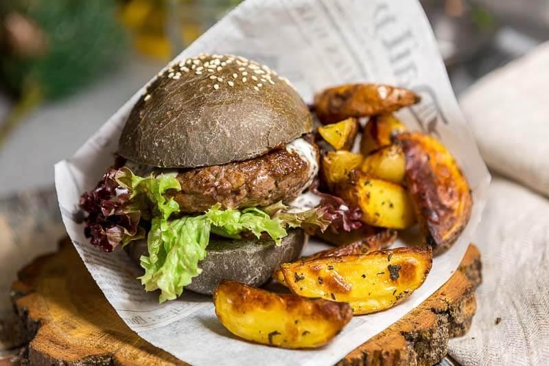 черный бургер с соусом из голубого сыра и картофельными дольками