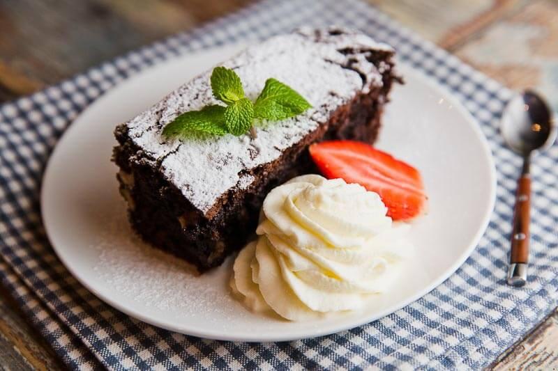 Брауни с пеканом и вяленой вишней, украшенный свежими ягодами
