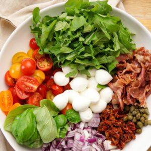 Салат с сочной рукколой, пармской ветчиной, вялеными томатами и моцареллой